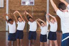 Teacher teaching exercise to school kids in basketball court stock photography