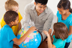 Teacher teaching geography. Cheerful elementary school teacher with a globe teaching geography Stock Photos