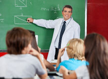 Teacher Teaching Geometry To Schoolchildren. Mature male teacher teaching geometry to schoolchildren in classroom Stock Image