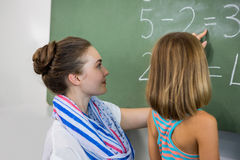 Teacher teaching girl on chalkboard in classroom Royalty Free Stock Images