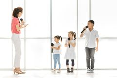 Teacher teaching group of kids to sing stock images