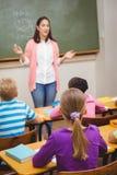 Teacher teaching her classroom of students Stock Photo