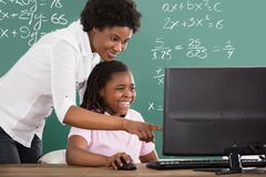 Teacher Teaching Her Student In Class. Smiling African Teacher Teaching Her Student On Computer In Class royalty free stock photography