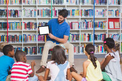 Teacher teaching kids on digital tablet in library. At elementary school Stock Photo