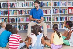Teacher teaching kids on digital tablet in library. At elementary school Royalty Free Stock Images