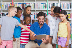 Teacher teaching kids on digital tablet in library. At elementary school Royalty Free Stock Photos