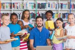 Teacher teaching kids on laptop in library Stock Photos
