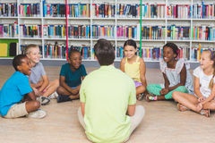 Teacher teaching kids in library. At elementary school stock photo