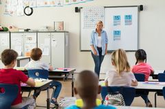 Teacher teaching math to children. Teacher teaching how to count on whiteboard in the classroom. Woman teaching math to elementary students sitting in class Stock Photo