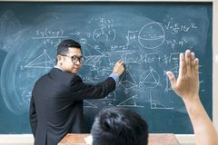 The teacher is teaching mathematics. Raising hand at class lesson, primary school scene. Success and education concept Stock Photos