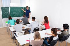 Teacher teaching mathematics to college students Royalty Free Stock Image
