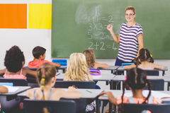Teacher teaching mathematics to school kids in classroom Royalty Free Stock Photos