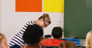 Teacher teaching mathematics to school kids in classroom stock footage