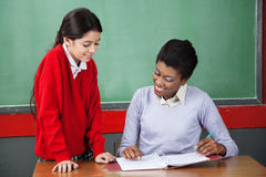 Teacher Teaching Schoolgirl At Desk Royalty Free Stock Photos