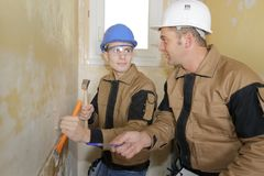 Teacher teaching student to use chisel and hammer. Teacher teaching student to use a chisel and hammer Royalty Free Stock Image
