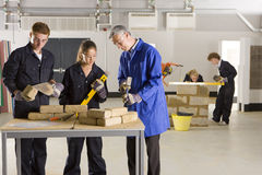Teacher teaching students bricklaying in vocational school Royalty Free Stock Image