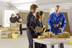 Teacher teaching students bricklaying in vocational school stock photos