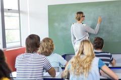 Teacher teaching students in class. Female teacher teaching students in the class Stock Photos
