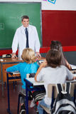 Teacher Teaching Students In Classroom Stock Images