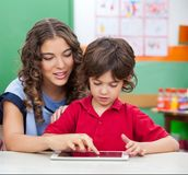 Teacher Teaching Students To Use Digital Tablet. Young teacher teaching students to use digital tablet in classroom Stock Images