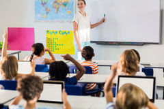 Teacher teaching students using whiteboard. Smiling female teacher teaching students using whiteboard in classroom Royalty Free Stock Photography