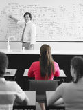 Teacher Teaching To Students In Class. Teacher teaching on whiteboard to high school students in classroom Royalty Free Stock Photo