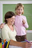 Teacher teaching young student in classroom. Back to school - teacher teaching 8 year old student in classroom Royalty Free Stock Images