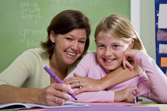 Teacher teaching young student in classroom Stock Images