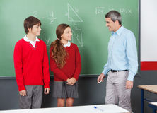 Teacher And Teenage Students Looking At Each Other. Mature male teacher and teenage students looking at each other standing by board in classroom Royalty Free Stock Images
