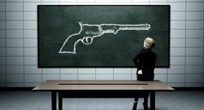 Teacher thinking about school safety. Teacher drawing a gun on the chalkboard Stock Images