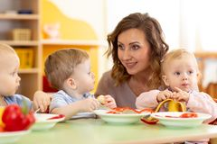 Teacher and three preschoolers having break for fruits and vegetables stock photography