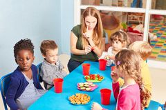 Teacher together with children while eating stock image