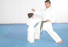 Teacher training karate to a little girl Stock Photo