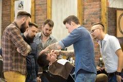 Teacher training students in beard shaving royalty free stock image