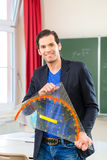 Teacher  with triangle in front of a school class Royalty Free Stock Image
