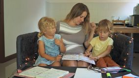 A teacher, a tutor for homeschooling. a teacher or mom at the table with little girl and boy. Homeschooling concept.  stock video