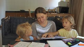 A teacher, a tutor for homeschooling. a teacher or mom at the table with little girl and boy. Homeschooling concept.  stock footage