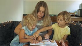 A teacher, a tutor for homeschooling. a teacher or mom at the table with little girl and boy. Homeschooling concept.  stock video footage
