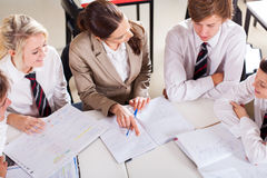 Teacher tutoring students. High school teacher tutoring group of students in classroom Stock Photos