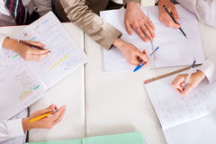Teacher tutoring students. Overhead view of teacher tutoring students in classroom Stock Image