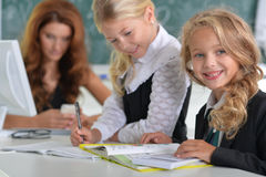 Teacher with two girls at lesson. Portrait of teacher with two girls at lesson Royalty Free Stock Photography