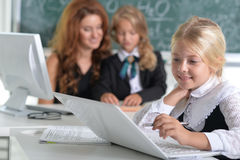 Teacher with two girls at lesson Stock Photos