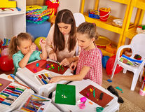 Teacher and two kids  mold from plasticine  in kindergarten . Royalty Free Stock Image