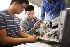 Teacher With Two Male College Students Building Machine In Science Robotics Or Engineering Class royalty free stock image
