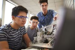 Teacher With Two Male College Students Building Machine In Science Robotics Or Engineering Class stock images