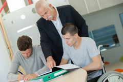 Teacher with two students one sitting in wheelchair. Teacher with two students one is sitting in a wheelchair Stock Photo