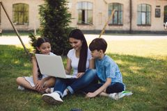 Teacher and two young students use laptop in park royalty free stock images