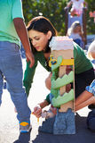 Teacher Tying Male Pupils Shoelace in Playground Stock Image