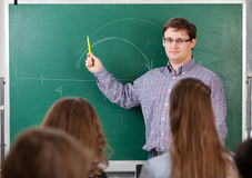 Teacher at university. In front of a chalkboard royalty free stock image