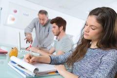 Teacher at university with students taking notes. Teacher Stock Photos